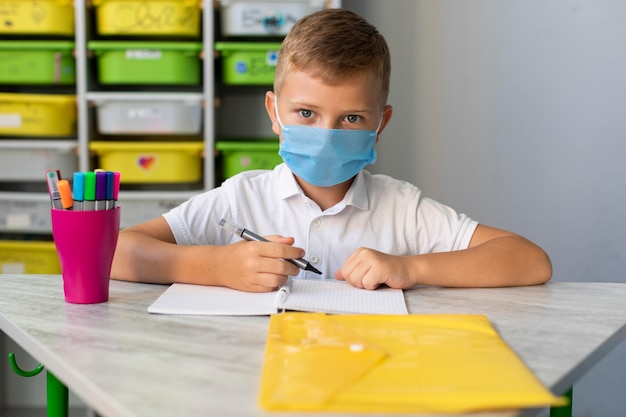 Kid draagt een gezichtsmasker in pandemische tijd