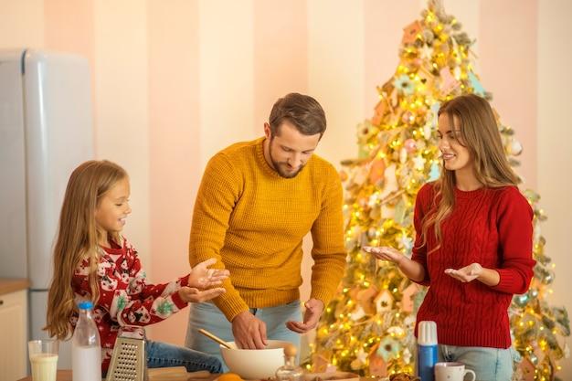 Kid en haar ouders koken samen in de keuken