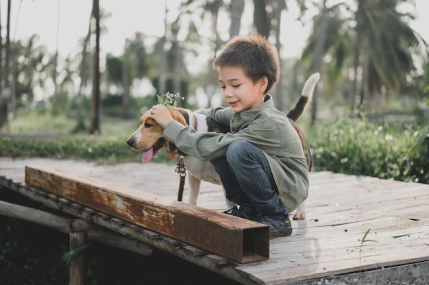 Kid en hond levensstijl in het park. kleine jongen samen met huisdier als beste vriend. outdoor activiteit op zomervakantie.