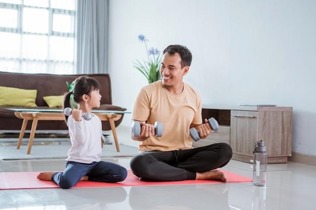 Kid en zijn vader doen oefening gewichtheffen thuis samen. aziatische jonge ouder met dochter