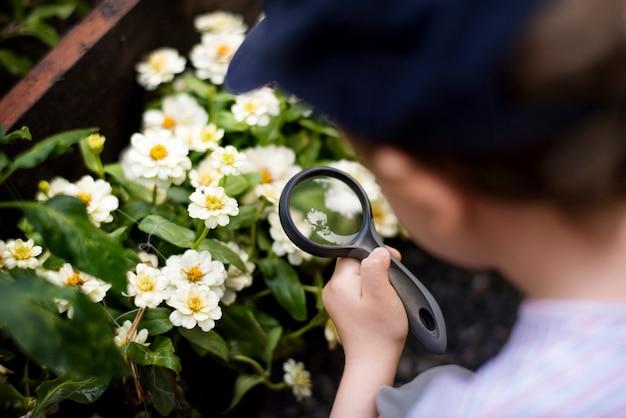 Kid gebruikt vergrootglas op zoek naar een bloem