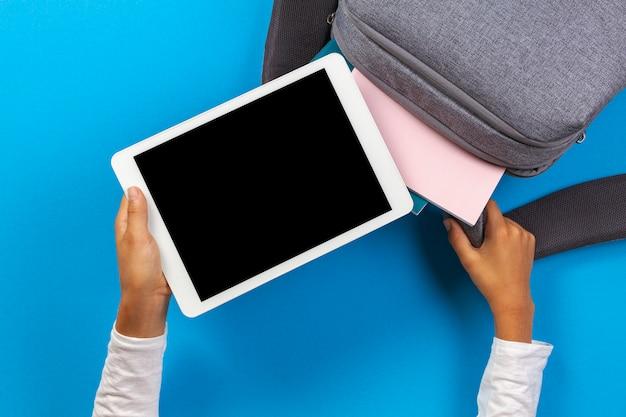 Kid hand met een witte tablet op een blauwe achtergrond