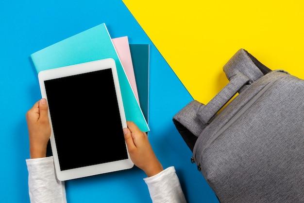 Kid hand met een witte tablet op een kleurrijke achtergrond