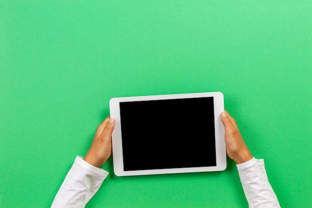 Kid handen met een witte tablet op een groene achtergrond