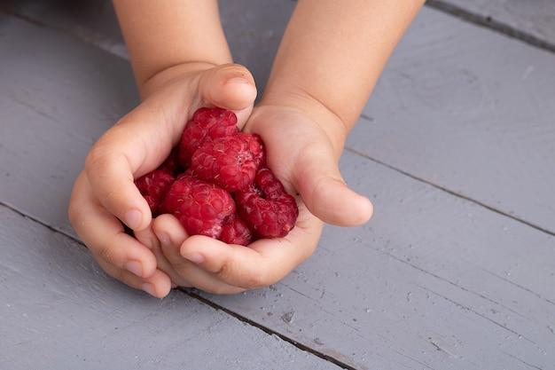 Kid holding aardbeien in handen, bovenaanzicht