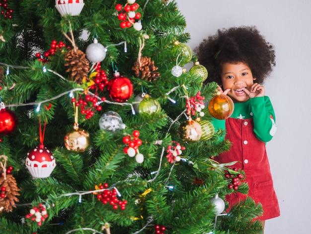 Kid is blij en grappig om kerstmis te vieren met een kerstboom