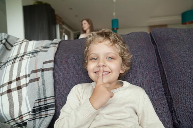 Kid jongen bedrijf vinger op lippen spelen verstoppertje
