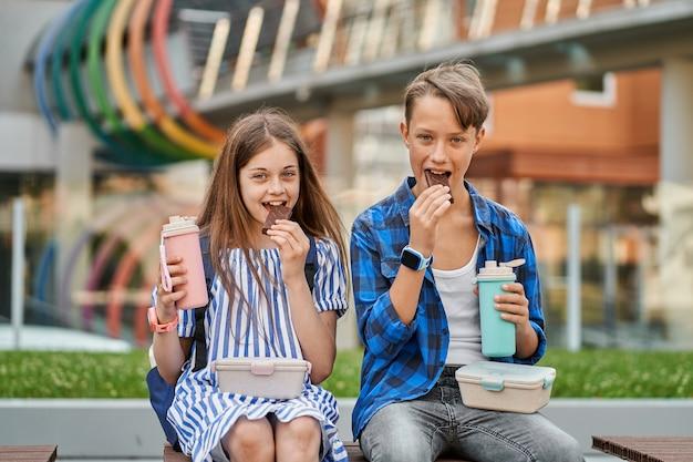 Kid jongen en kind meisje chocolade eten en thee drinken met lunchbox en thermoskan.