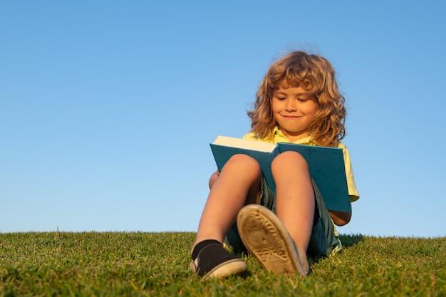 Kid jongen lees boek in het park.