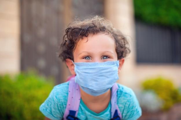 Kid jongen met medische gezichtsmasker buiten blijven