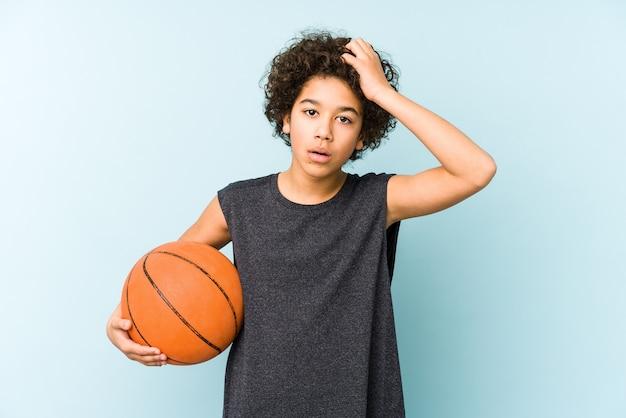 Kid jongen spelen basketbal geïsoleerd op blauwe achtergrond geschokt, ze heeft belangrijke bijeenkomst herinnerd.