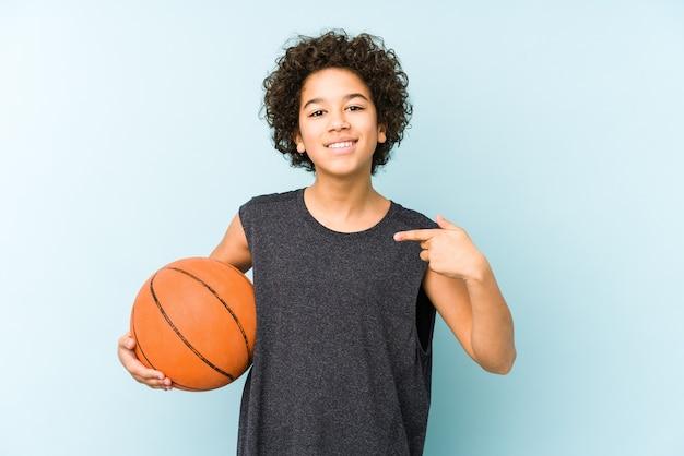 Kid jongen spelen basketbal geïsoleerd op blauwe achtergrond persoon met de hand wijzend naar een shirt kopie ruimte, trots en zelfverzekerd