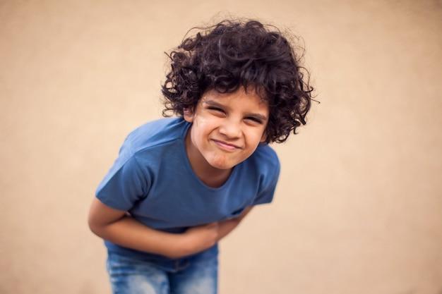 Kid jongen voelt sterke buikpijn. kinderen, gezondheidszorg en geneeskunde concept
