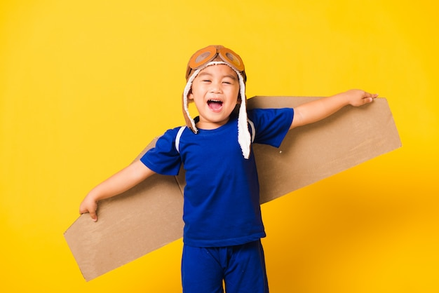 Kid jongetje glimlach dragen pilot hoed spelen en bril met speelgoed kartonnen vliegtuig vleugels