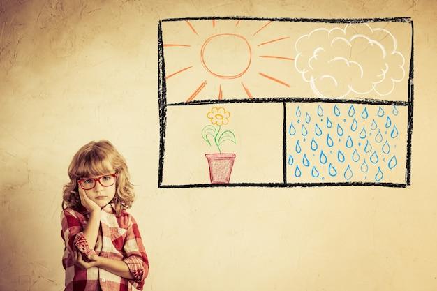 Kid kijkt uit het getekende open raam op grunge muur. vrijheidsconcept