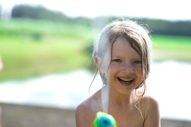 Kid kind, meisje speelt met waterpistool speelgoed in de zomer.