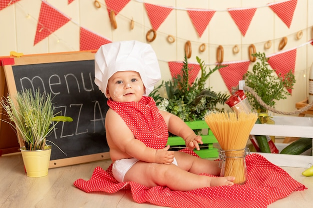 Kid kok, een klein kind in een koksmuts kookt spaghetti in de keuken