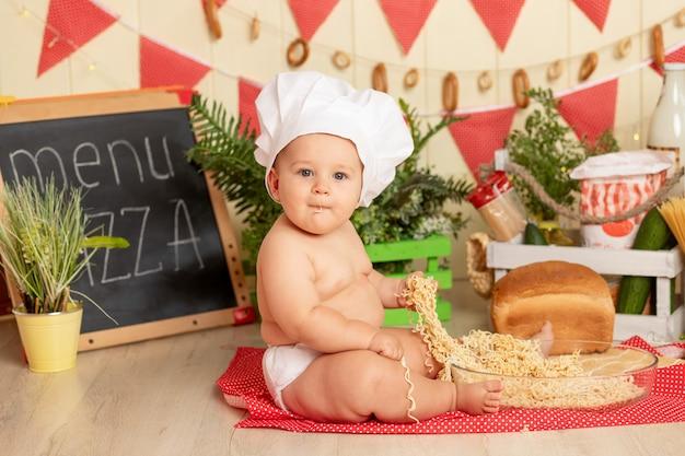 Kid kok, een klein kind kookt in een hoed in de keuken tussen de producten en eet spaghetti met zijn handen