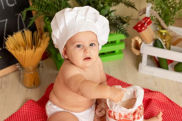 Kid kok, portret van een klein kind in een koksmuts in de keuken met bloem