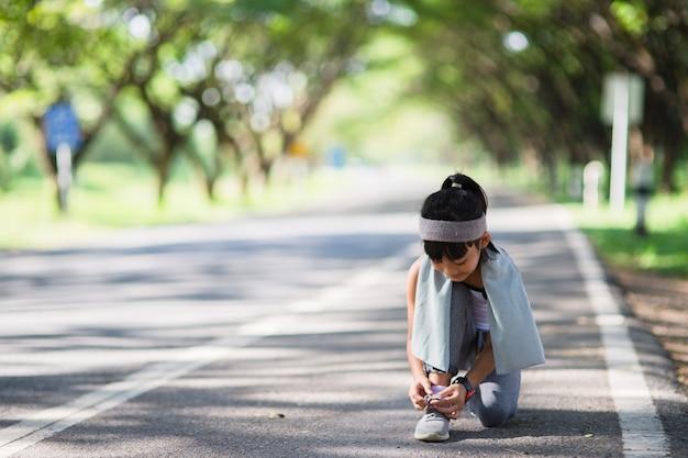 Kid koppelverkoop hardloopschoenen. gelukkig grappige kleine aziatische meisje fitness vrouw die 's ochtends loopt. atletisch jong kind dat in de natuur loopt. gezonde levensstijl