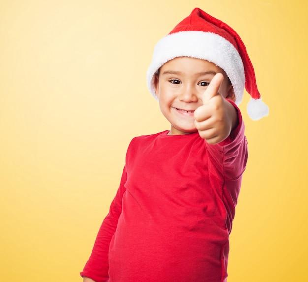 Kid lachend met duim omhoog en de hoed van santa