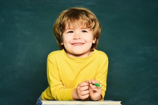 Kid leert in de klas op de achtergrond van het schoolbordonderwijsproces