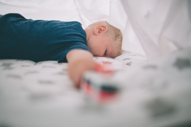 Kid ligt op de vloer. de jongen speelt thuis in de ochtend in speelgoedauto's. casual levensstijl in de slaapkamer.