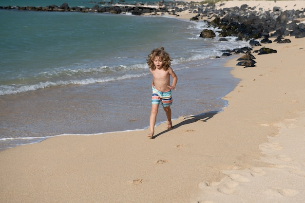 Kid loopt op het strand. gelukkig kind rennen in zee op zomervakantie. reizen en avontuur op zee of oceaan.