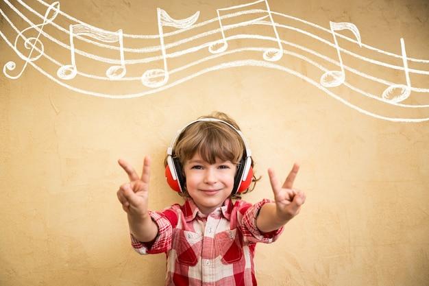 Kid luister muziek thuis. hipster kind met koptelefoon. retro muziekconcept