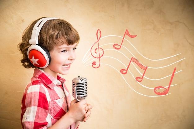 Kid luister muziek thuis. hipster kind met retro vintage microfoon