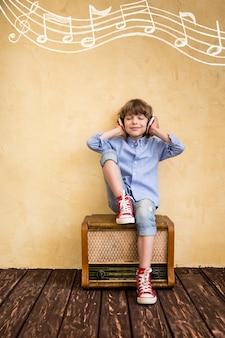 Kid luister muziek thuis. hipster kind met retro vintage radio
