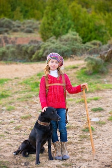 Kid meisje herderin blij met hond en kudde schapen
