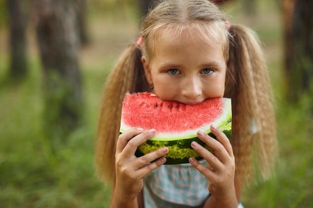 Kid meisje watermeloen eten in de tuin.