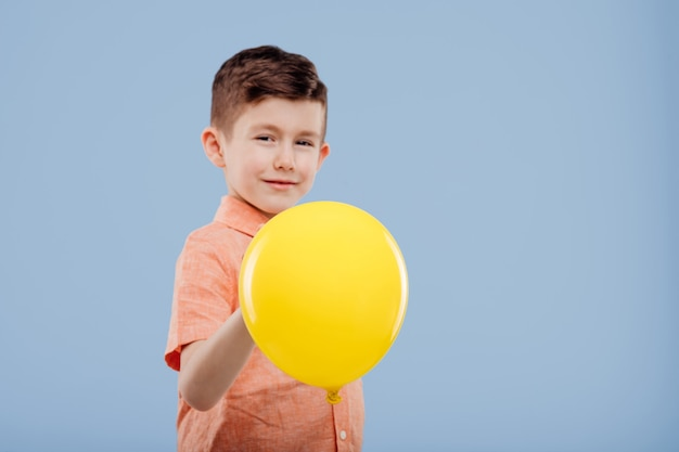 Kid met gele ballon, kijkt naar de camera, geïsoleerd op blauwe achtergrond, kopieer ruimte