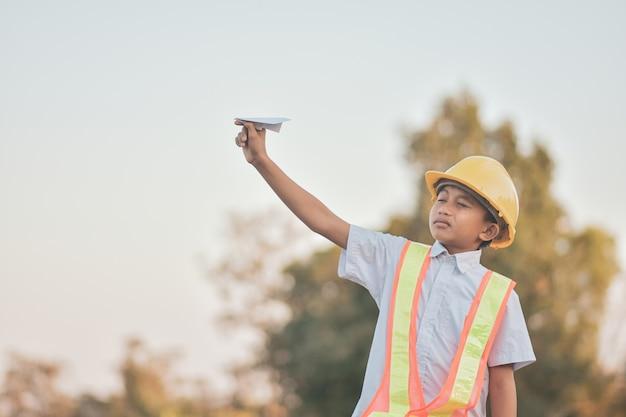 Kid met gele helm en papieren vliegtuigje