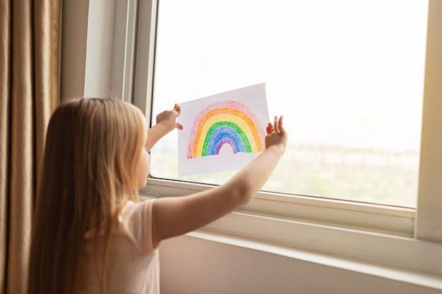 Kid met geschilderde regenboog tijdens covid-19 quarantaine in de buurt van venster