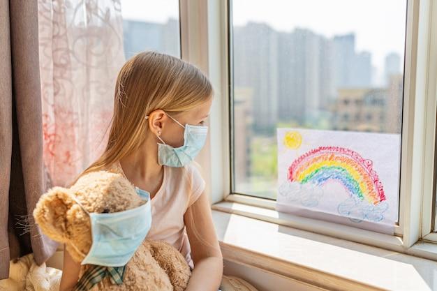 Kid met geschilderde regenboog tijdens covid-19 quarantaine thuis