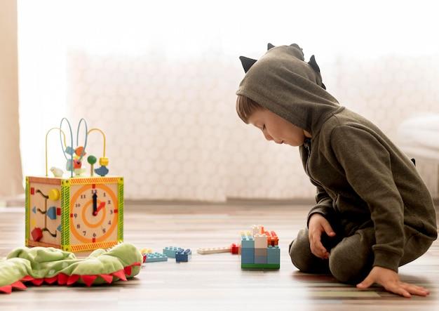 Kid met kostuum binnenshuis spelen