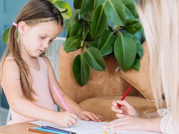 Kid met potloden thuis tekenen