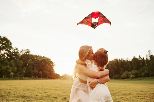 Kid met vlieger wanneer moeder haar kust. plezier in het veld. prachtige natuur.