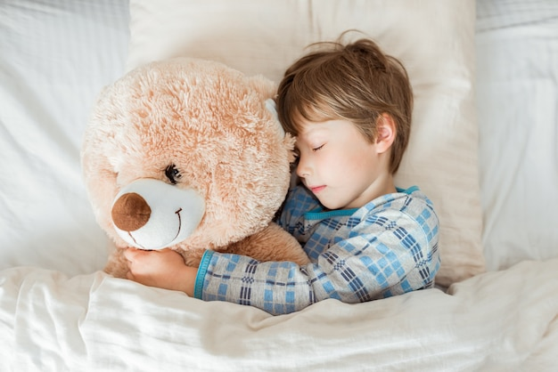 Kid op bed slapen, gelukkig slapengaan in witte slaapkamer