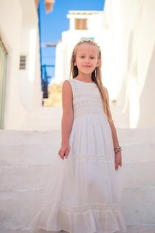 Kid op straat van typisch grieks traditioneel dorp met witte muren en kleurrijke deuren op het eiland mykonos