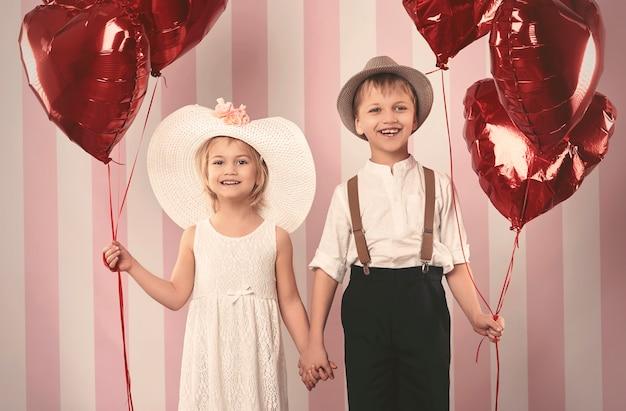 Kid paar en een heleboel ballonnen Gratis Foto