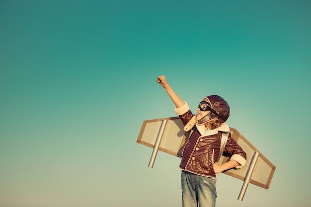 Kid piloot met speelgoed jet pack tegen herfst hemelachtergrond. gelukkig kind buiten spelen