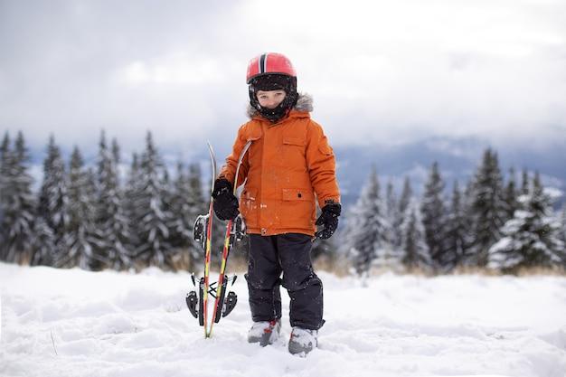 Kid poseren met ski-uitrusting in de sneeuw