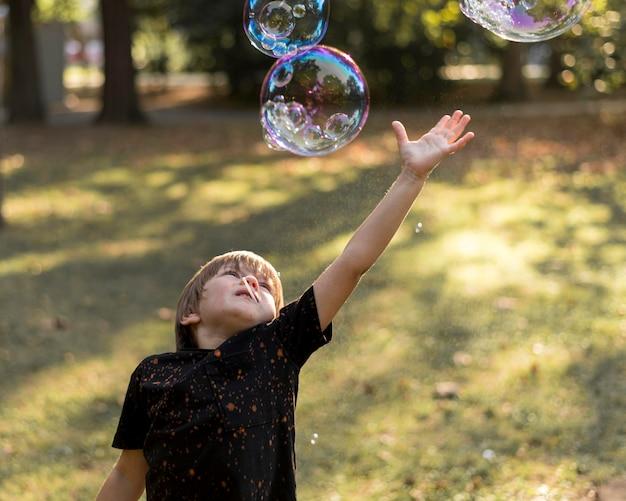 Kid probeert zeepbellen te vangen