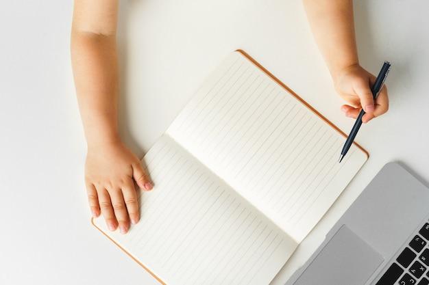 Kid's handen schrijven in notitieblok geopend, bovenaanzicht