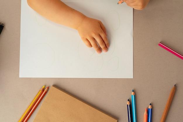 Kid's handen schrijven in notitieblok openen, bovenaanzicht, kopieer ruimte