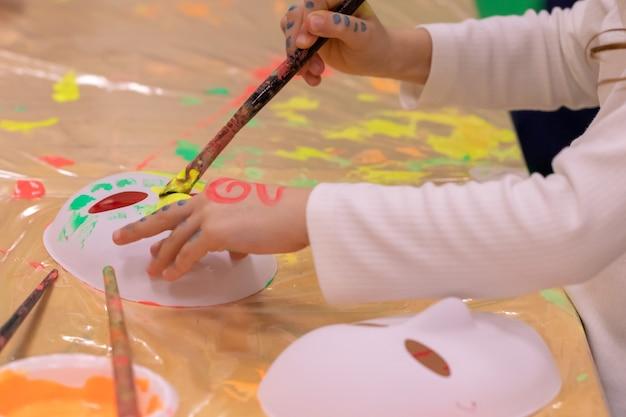 Kid schilderen en tekenen op masker.