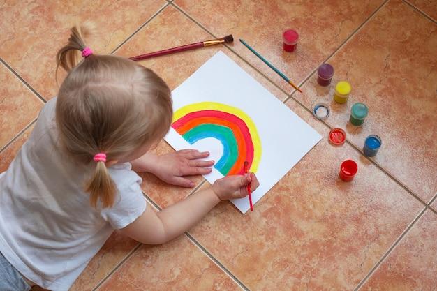 Kid schilderij regenboog thuis tijdens pandemische coronavirus quarantaine.